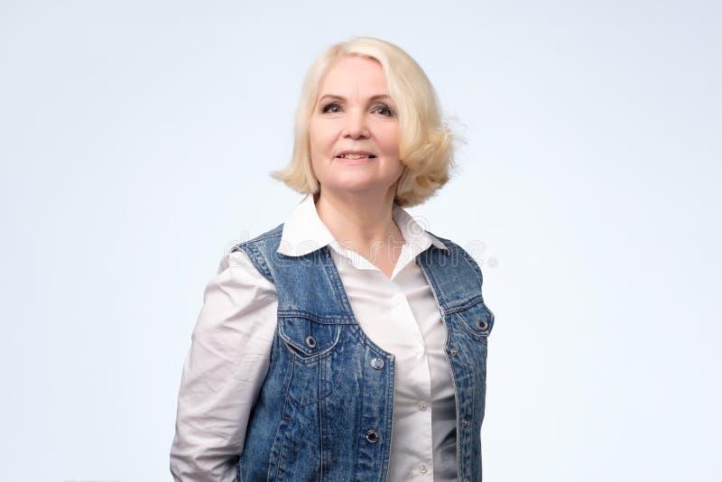 Femme blonde européenne supérieure de sourire regardant la caméra photographie stock