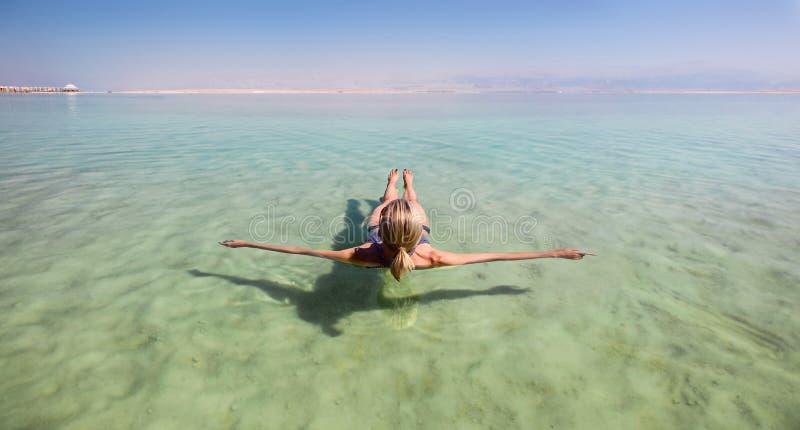 Femme blonde flottant dans les eaux de turquoise de la mer morte photographie stock