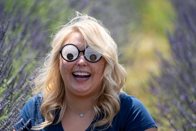 Femme blonde folle utilisant les lunettes de soleil écarquillées de nouveauté de yeux tout en se reposant dans un domaine de lava image libre de droits