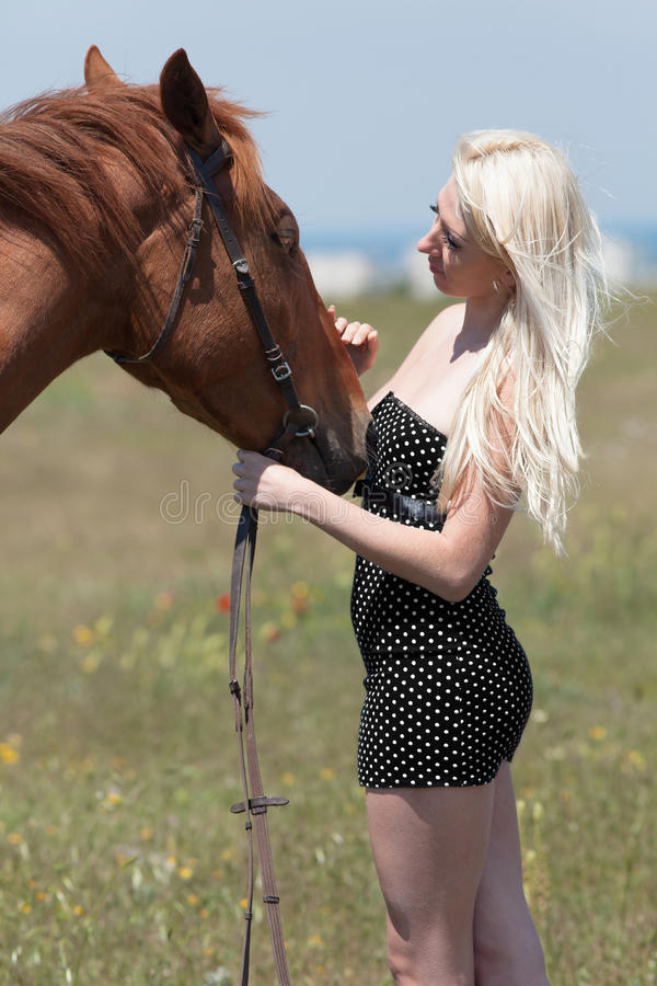 Femme blonde frottant le hongre image stock