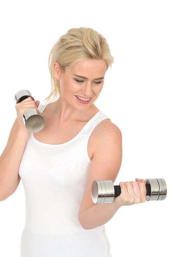 Femme blonde heureuse en bonne santé d'ajustement attrayant jeune établissant avec les poids muets de Bell images stock