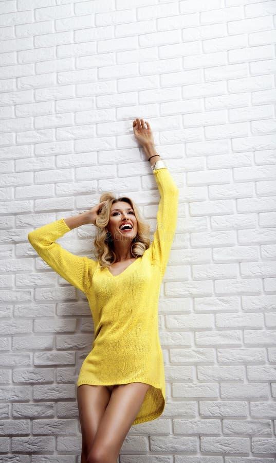 Femme blonde heureuse posant avec le sourire toothy. photographie stock libre de droits