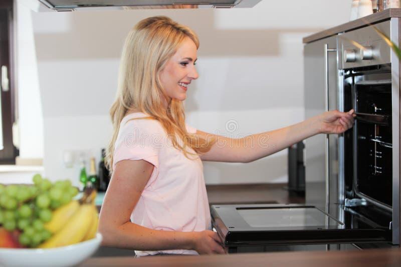 Femme blonde heureuse préparant la nourriture à la cuisine photo libre de droits