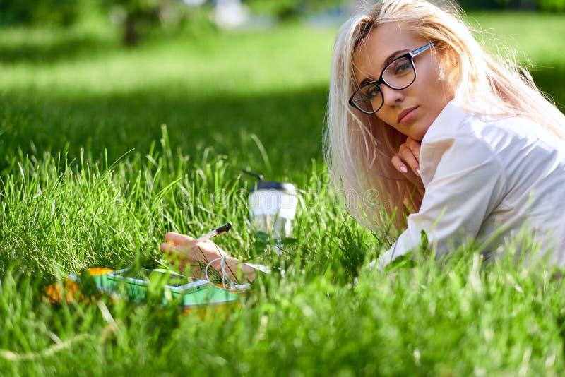 Femme blonde heureuse se trouvant sur l'herbe, souriant et tenant une tasse de caf? sur le pr? images libres de droits