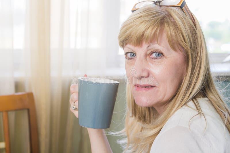 Femme blonde heureuse supérieure tenant la tasse de café images stock