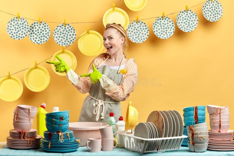 Femme blonde impressionnante émotive montrant ses plats propres sur les pinces à linge photo libre de droits