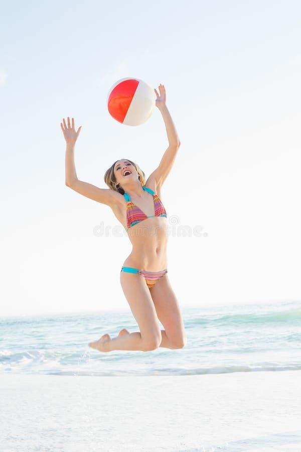 Femme blonde joyeuse jetant un ballon de plage images libres de droits