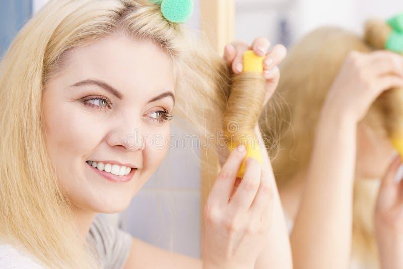 Femme blonde ? l'aide des rouleaux de cheveux photographie stock