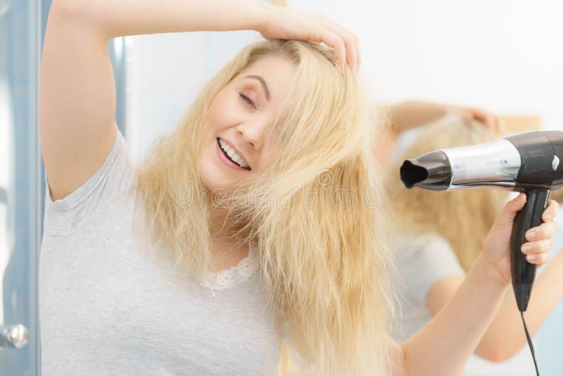 Femme blonde ? l'aide du s?che-cheveux photographie stock libre de droits