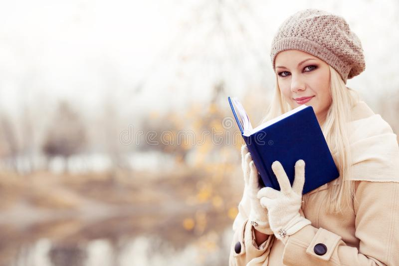 Femme blonde lisant un livre image stock