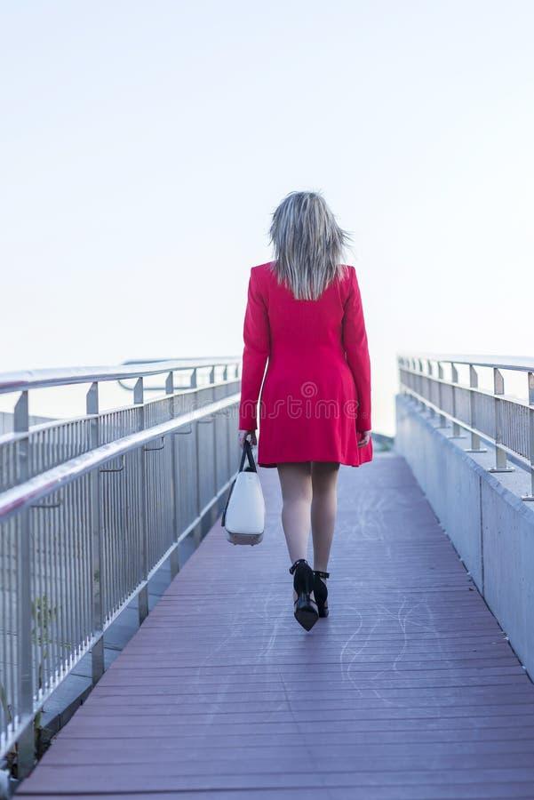 Femme blonde marchant loin au-dessus de l'emballement photos stock