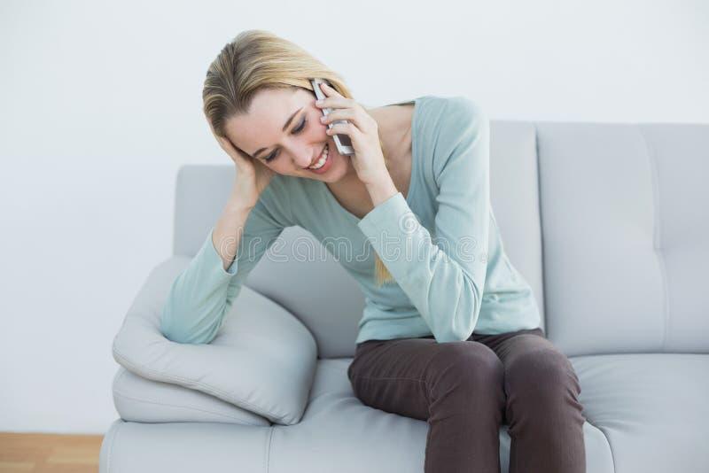 Femme blonde mignonne téléphonant se reposer heureusement sur le divan photographie stock