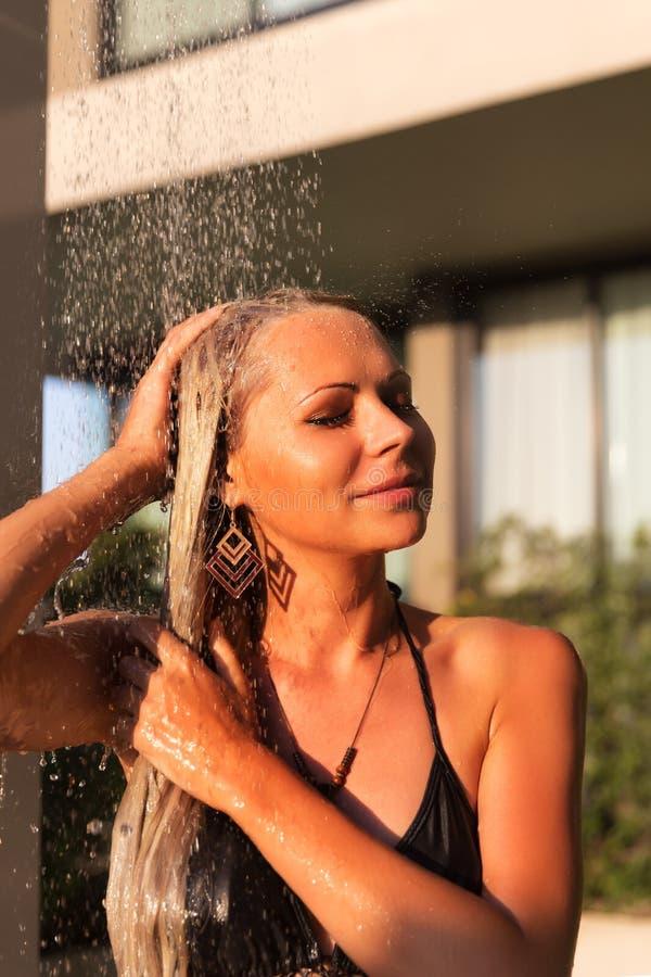 Femme blonde mince prenant la douche près de la piscine dehors image libre de droits