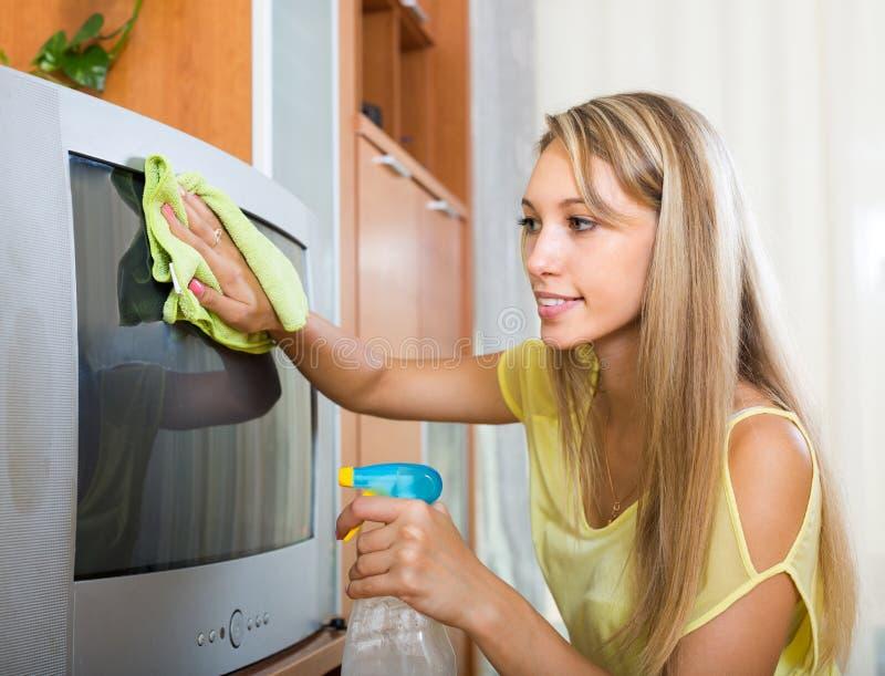 Femme blonde nettoyant la TV à la maison photographie stock libre de droits
