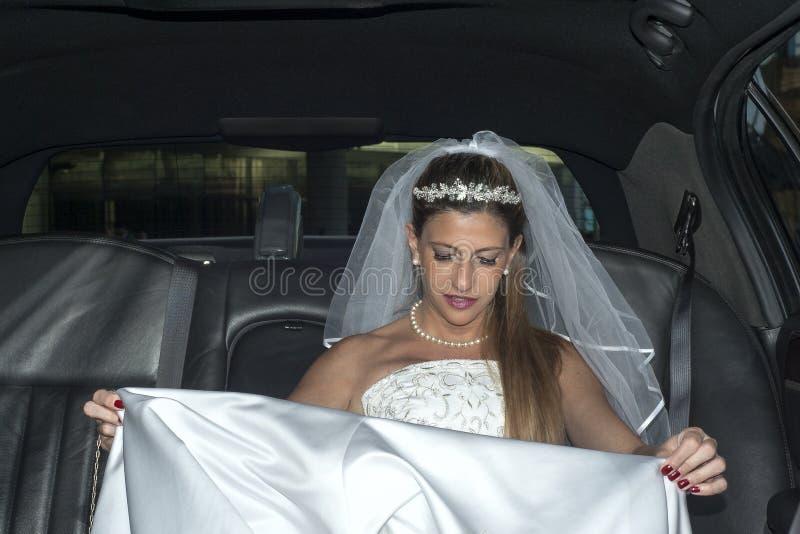 Femme blonde nuptiale sur la limousine photographie stock libre de droits