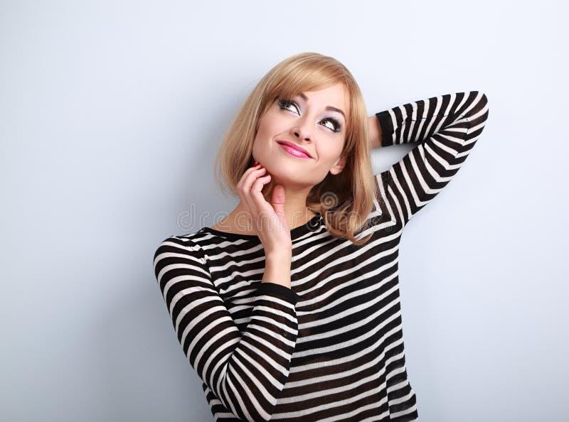 Femme blonde occasionnelle de pensée rayant le menton et détendant des toilettes image stock