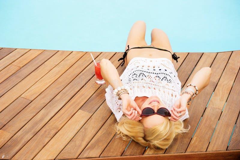 Femme blonde par la piscine en vacances images stock