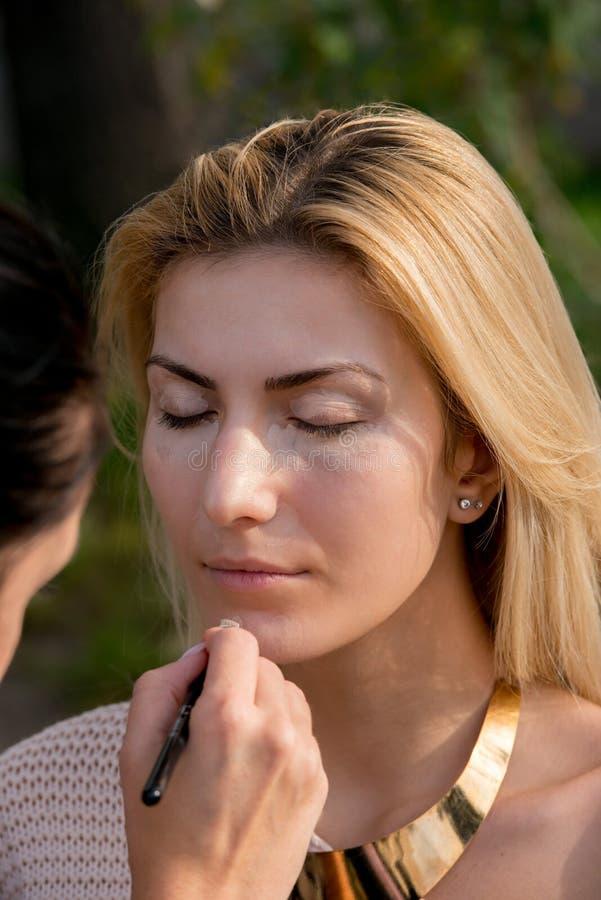 Femme blonde pendant une session de maquillage image stock