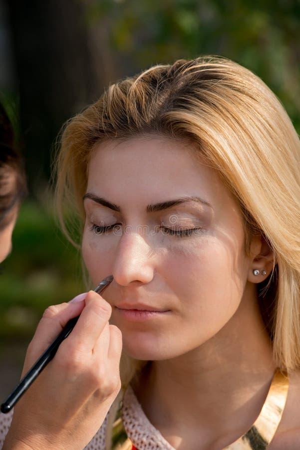 Femme blonde pendant une session de maquillage photographie stock