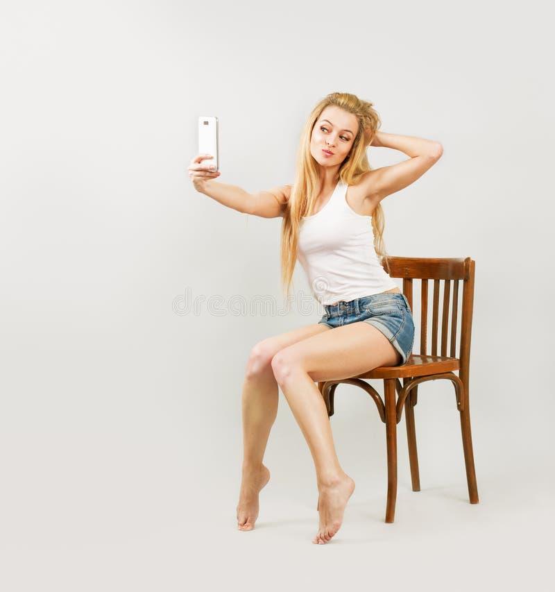 Femme blonde prenant l'autoportrait avec le téléphone image stock