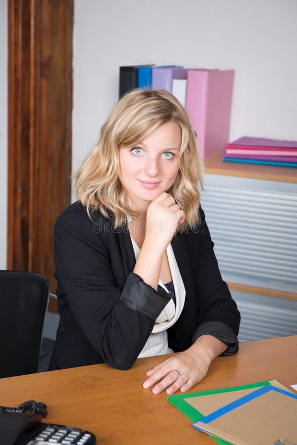 Femme blonde réussie d'affaires travaillant au regard de bureau photos libres de droits