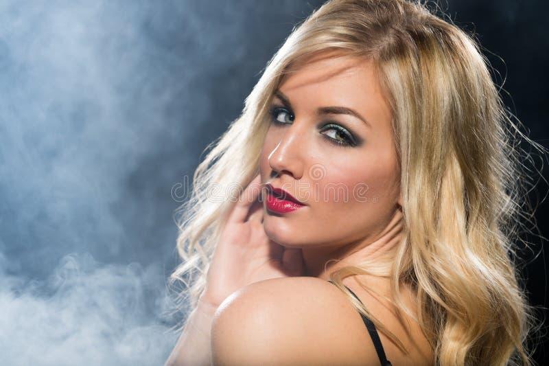 Femme blonde regardant au-dessus de son épaule photographie stock