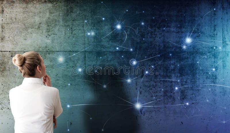 Femme blonde regardant la projection de la structure de réseau avec des noeuds rougeoyants sur le mur en béton rugueux photo stock
