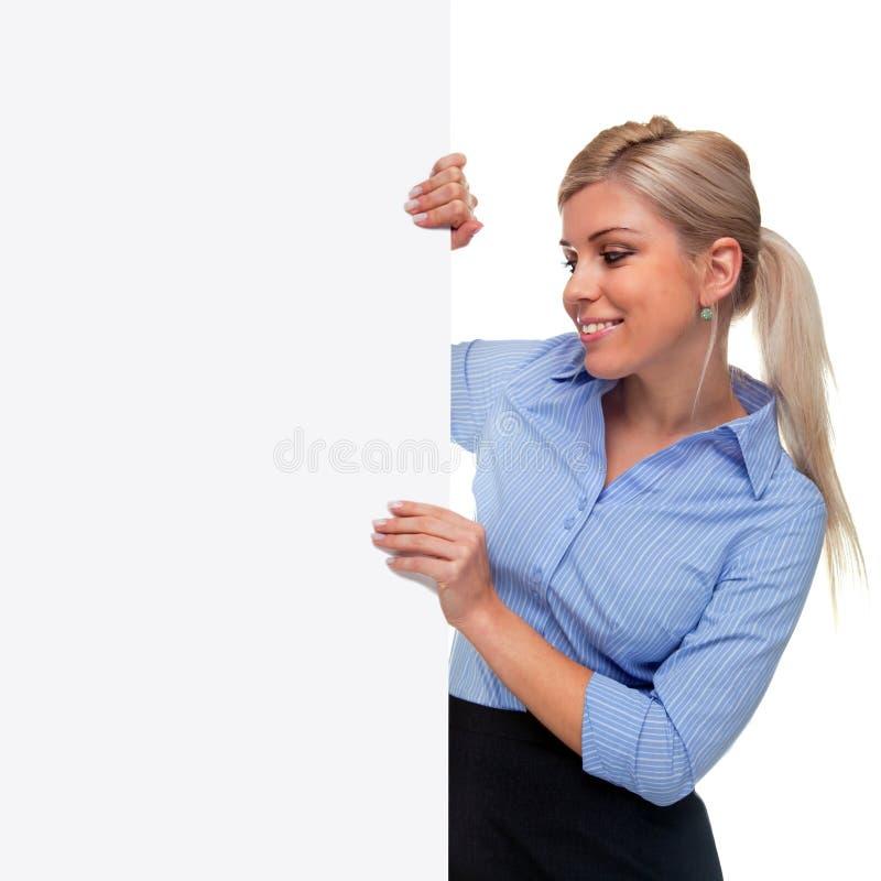 Femme blonde retenant le côté d'un panneau blanc de signe photos libres de droits