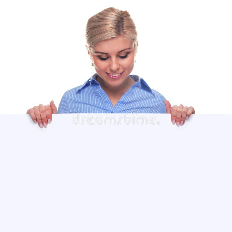 Femme blonde retenant un panneau de message blanc. images stock