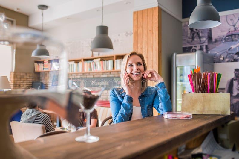 Femme blonde s'asseyant à la barre, parlant au téléphone images stock
