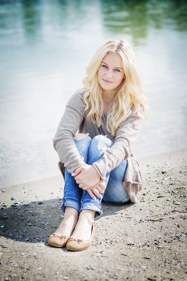 Femme blonde s'asseyant au lac image libre de droits