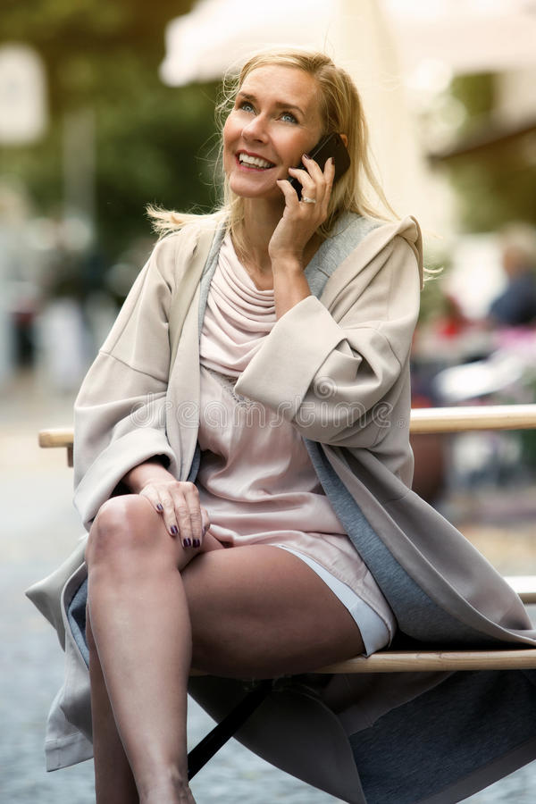 Femme blonde s'asseyant sur le banc et parlant au téléphone photographie stock