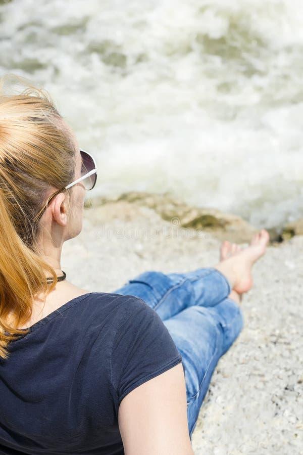 Femme blonde s'asseyant sur une plage rocheuse photos stock