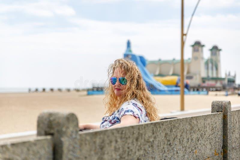 Femme blonde s'asseyant sur une plage tranquille en Angleterre photos libres de droits