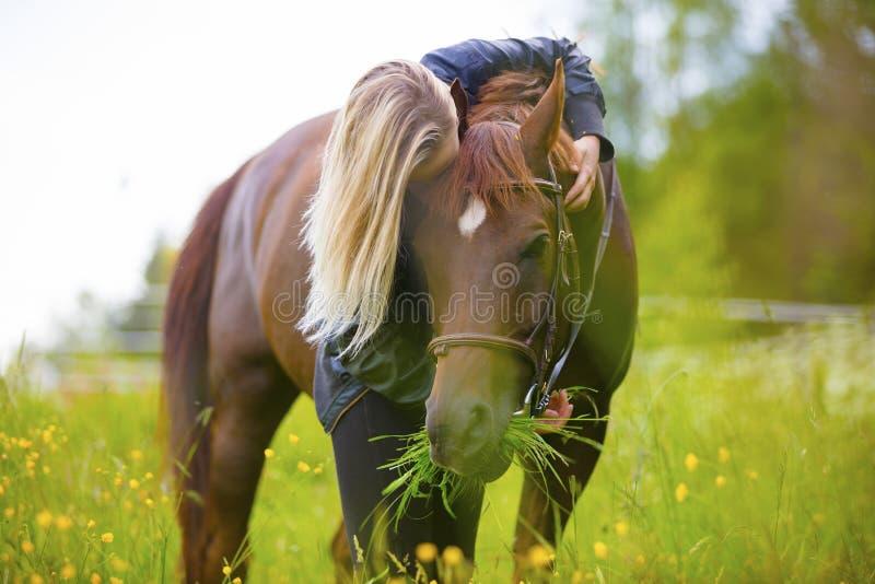 Femme blonde se tenant dans un pré étreignant son cheval Arabe image libre de droits