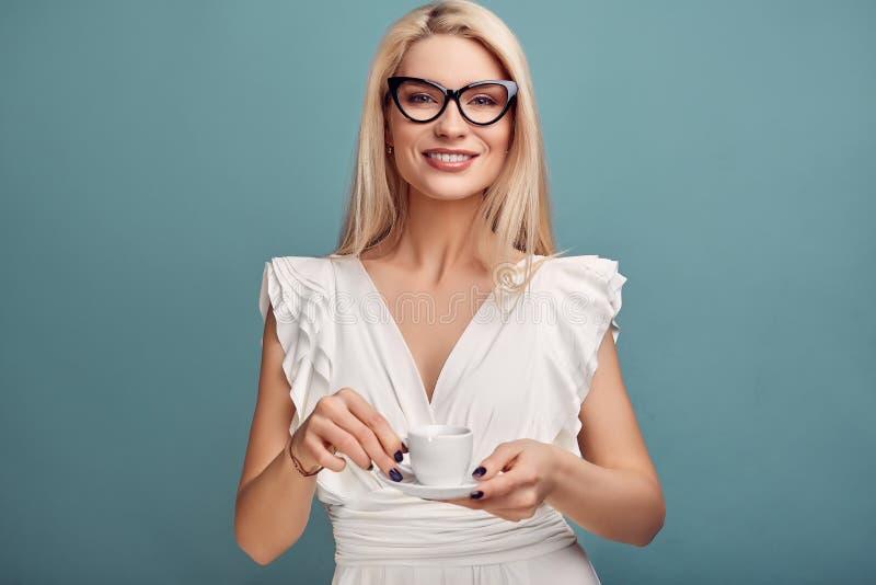 Femme blonde sensuelle magnifique dans la robe blanche avec la tasse de café photos stock