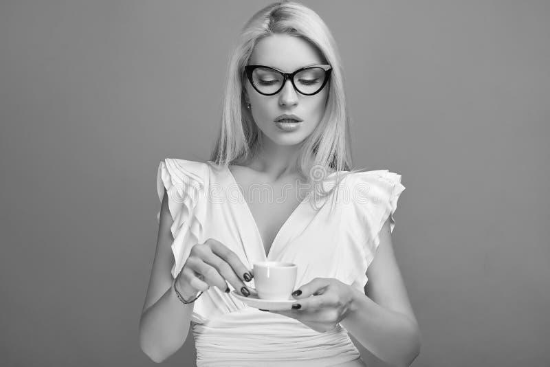 Femme blonde sensuelle magnifique dans la robe blanche avec la tasse de café image stock