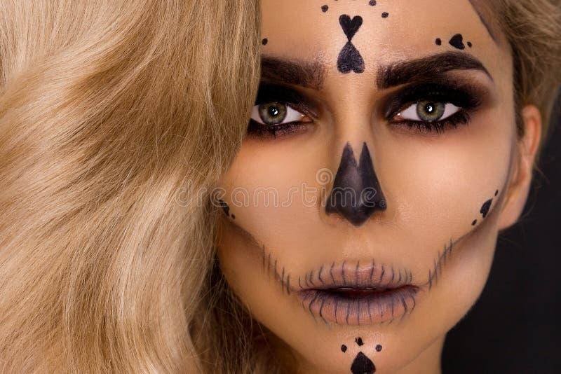Femme blonde sexy dans le maquillage de Halloween et équipement en cuir sur un fond noir dans le studio Squelette, monstre images stock