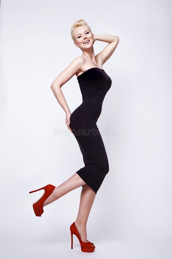 Femme blonde sexy de beauté dans le corps parfait de pin-up de robe noire maigre images stock