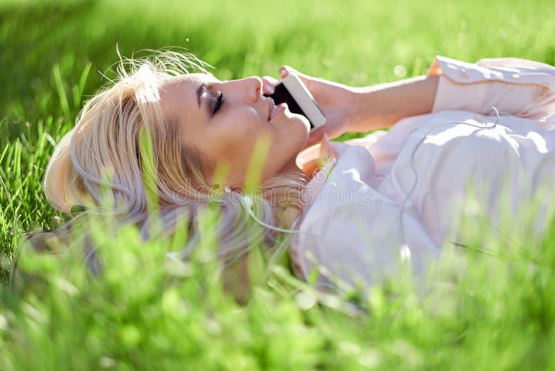 Femme blonde sexy parlant au téléphone portable et se trouvant sur le pré photographie stock libre de droits