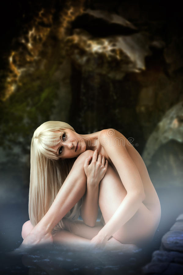 Femme blonde sexy s'asseyant dans l'eau de lagune images libres de droits
