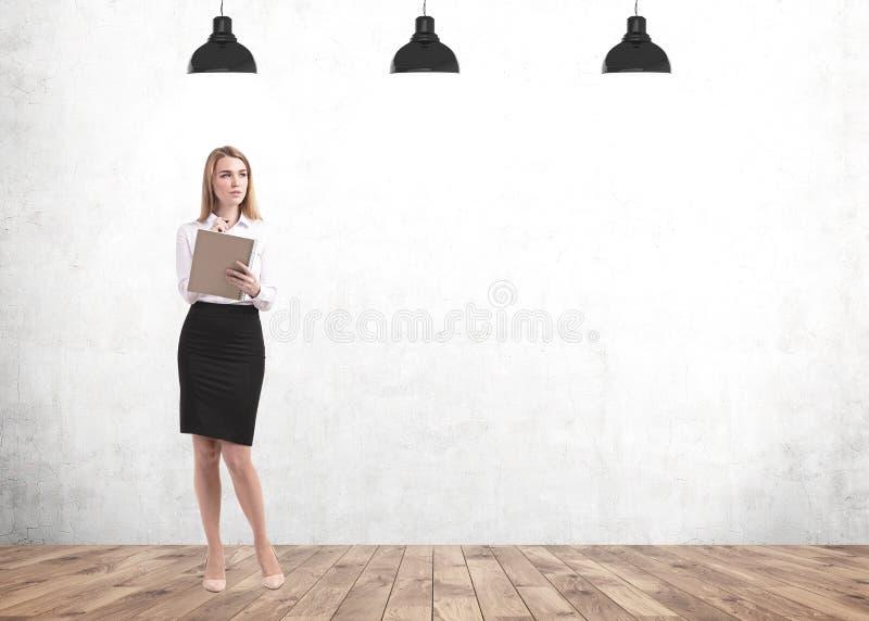 Femme blonde songeuse réévaluant dans le cahier, faux photographie stock libre de droits