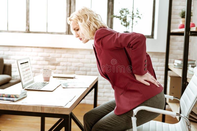 Femme blonde soumise à une contrainte ayant le mal de dos extrême au travail photographie stock