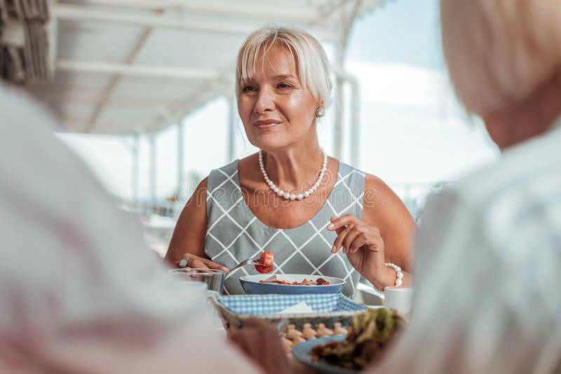 Femme blonde stup?fiante mangeant de sa nourriture saine images stock
