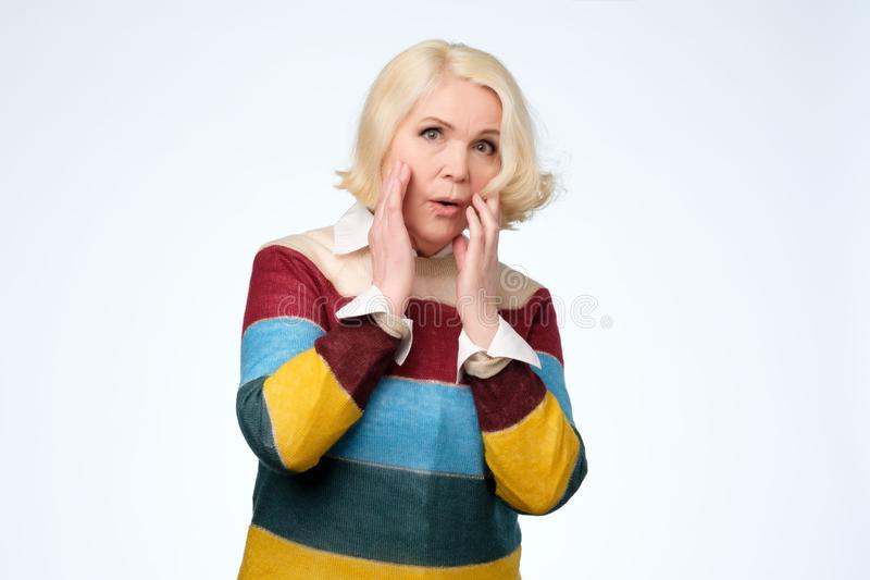 Femme blonde supérieure disant wouah touchant le visage et haletant photos libres de droits