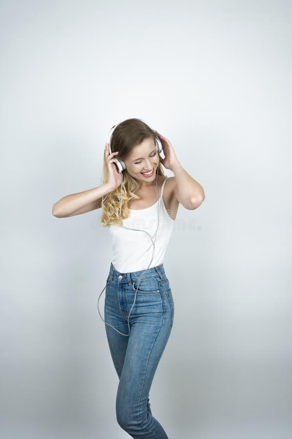 Femme blonde tenant ses écouteurs avec les deux mains écoutant le fond blanc de sourire de musique image libre de droits