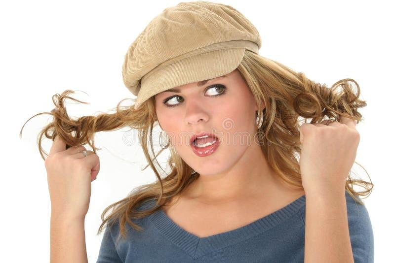 Femme blonde tordant le cheveu photo stock