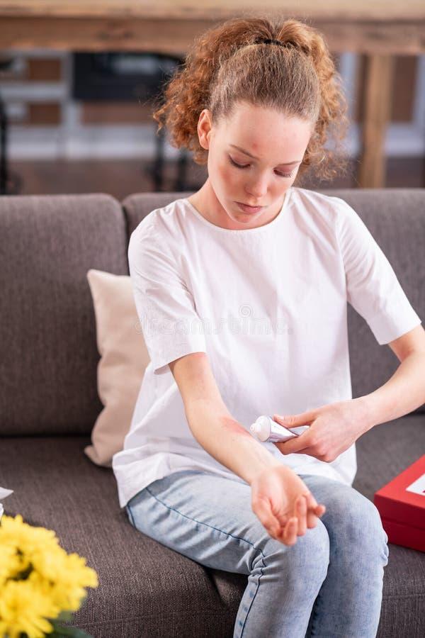 Femme bouclée attentive couvrant son irritation allergique en main photographie stock