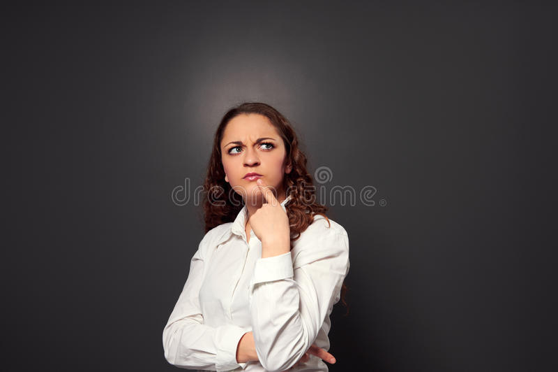 Femme bouclée drôle pensant à quelque chose image stock