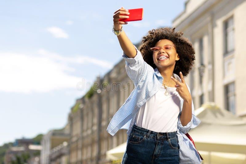 Femme bouclée joyeuse prenant le selfie et montrant le signe de V photos libres de droits
